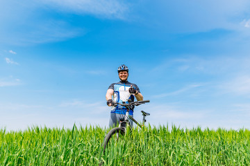 young adult smiling man standing with bicycle in green barley fi