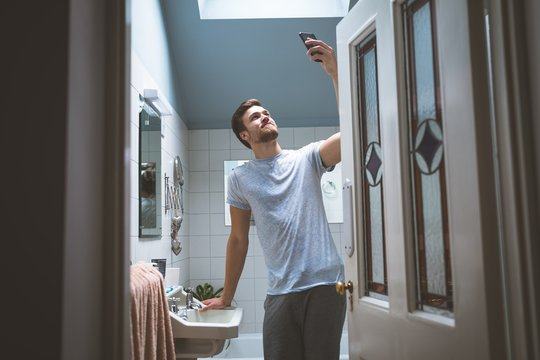 Woman taking selfie with mobile phone in bedroom