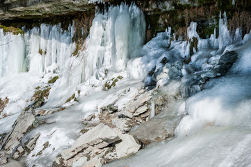 Icicles create a beautiful wall of ice over a rock ledge. Jagala Waterfall, Estonia.