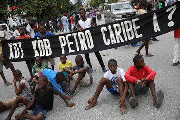 "A group of children sit next to a banner that reads ""Where is the PetroCaribe money?"" during a protest to demand an investigation into the alleged misuse of Venezuela-sponsored PetroCaribe funds by previous administrations, in Port-au-Prince"