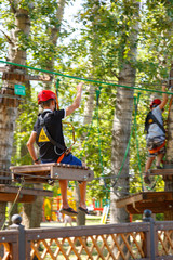 Boy with climbing gear in an adventure park are engaged in rock climbing or pass obstacles on the rope road. Rope park in pine wood forest against the sky