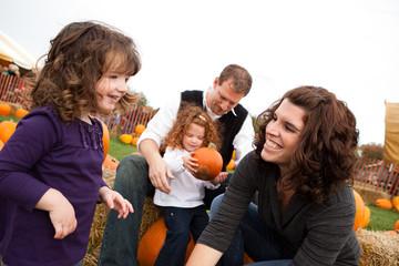 Happy Family in Pumpkin Patch in Autumn