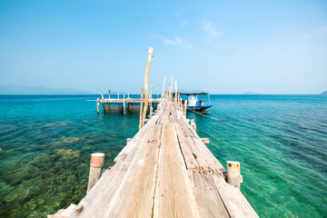 Seascape with pier and small fishing boat. Beautiful view from the wooden pier on the azure sea coast. The crystal clear water of the coast on an island in Thailand.