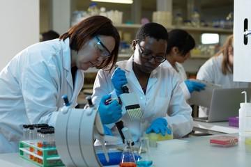 Female scientists using pipette in laboratory
