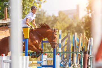Young man riding horse on show jumping event. Sportsman on his course in equestrian competition