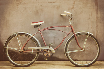 Aluminium Prints Bicycle Vintage rusted cruiser bicycle on a wooden floor