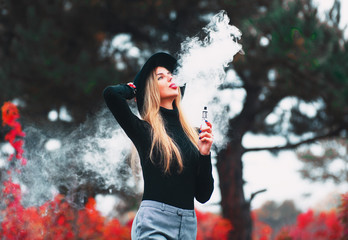 Young girl in black hat vaping vape device with cloud of vape outdoors in autumn.