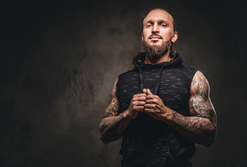 Portrait of a bearded tattooed athlete in a black hoodie. Isolated on a dark textured background.