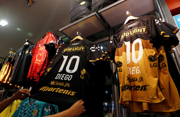"""A shop vendor shows a Dorados soccer club jersey for sale with the name """"Diego"""" and number """"10"""" in Culiacan"""