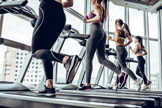 Side view of young beautiful women looking away while running on treadmill at gym