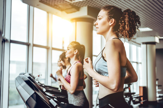 Beautiful young cheerful woman in sportswear running on treadmill at gym with other women