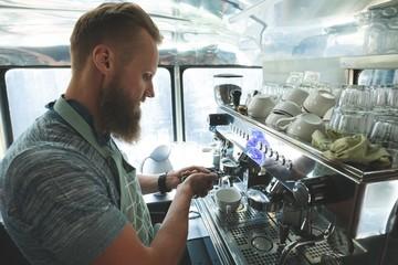 Waiter preparing coffee in food truck