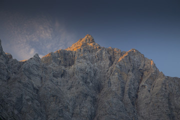 The steep north face of the Triglav in Slovenia is turning orange by the rising sun.