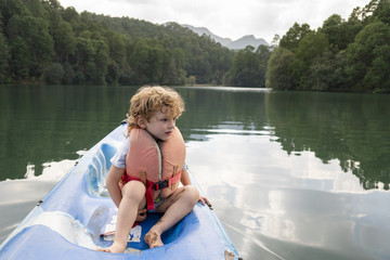 A two years old boy sitting on a kayak at Rancho Santa Elena, Hidalgo, Mexico,