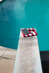 Looking down on folded red and white striped beach towel folded on a diving board with a book, sunscreen, and aviator sunglasses on top. Swimming pool in the backyard with folded towel on diving board