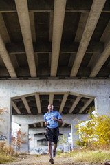 Man jogging under bridge, Birmingham, Alabama, USA