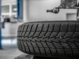 Wheel whit winter tire on tire changing machine in a workshop. Wheel on tire changing machine. White car in background.