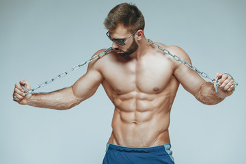 .bodybuilder posing. Beautiful sporty guy male power. Fitness muscled in blue shorts and sunglasses. on isolated grey background. Man with muscular torso. Strong Athletic Man Fitness Model Torso