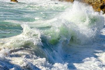 gros plan sur un rouleau de vague qui s'écrase avec de l'écume