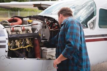Engineer servicing aircraft engine near hangar