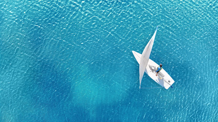 Aerial. Little sailing ship on a crystal blue water. Navigation concept.