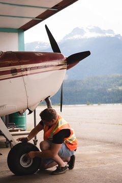 Mechanic servicing aircraft landing gear