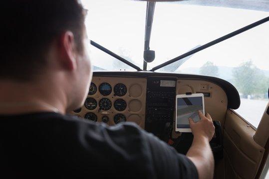 Pilot using digital tablet in cockpit