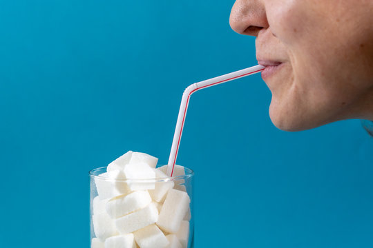 Profile of a young woman drinking with a red stripes straw from a glass filled with sugar cubes on blue background. Junk food, unhealthy diet, too much sugar on drinks, nutrition concept