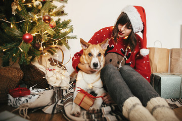 happy girl in santa hat hugging with cute dog on background of golden beautiful christmas tree with lights and presents and gifts in festive room. family warm  moments