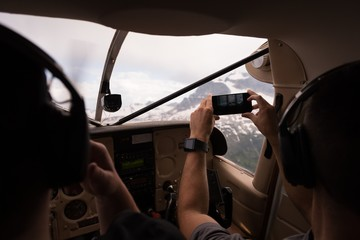 Pilot taking photos with mobile phone while flying
