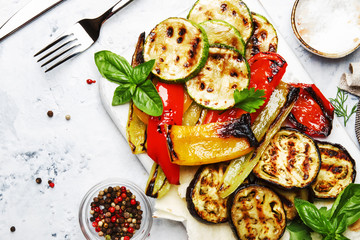 Grilled colorful vegetables, aubergines, zucchini, pepper with spice and green basil on serving board on white background, top view Wall mural
