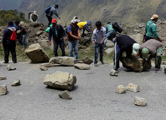 Coca growers move stones blocking a road between La Paz and Los Yungas region to protest against government in Unduavi