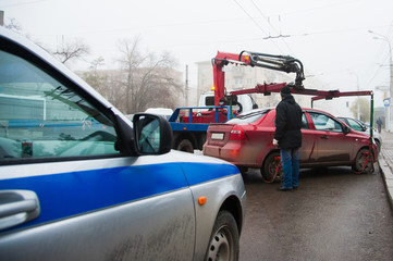 Traffic police officers on the street lifting the car on the tow truck