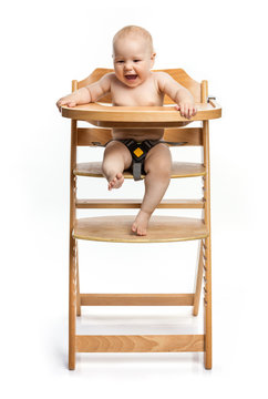 Happy cute baby girl sitting in high chair over white