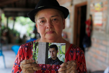 Lidia Urias shows a picture of her son David at her farm in San Isidro