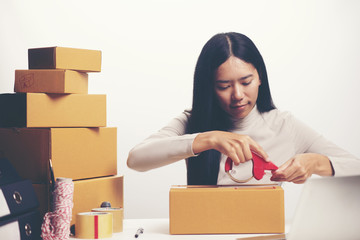Female hands packing box at warehouse, online marketing concept