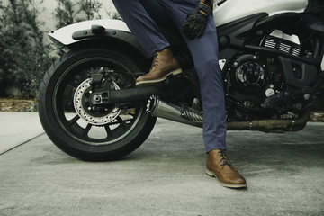 Men's legs in classic leather shoes on motorcycle background