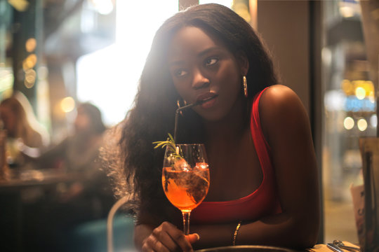 Beautiful girl drinking a cocktail in a bar