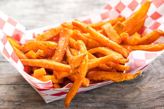 Paper basket of sweet potato fries with salt on rustic wooden table
