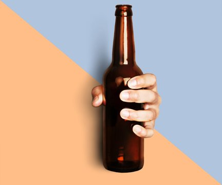 Hand holding beer bottle without label isolated on white