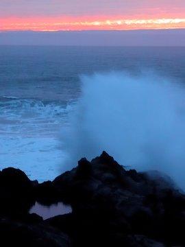 Thundering shores surf crashing on rocky shoreline at sunset Oregon coast