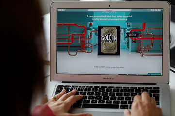 A worker at the studio's of Wonderbly interactive book publisher, demonstrates the process of ordering The Golden Ticket interactive book online, in London