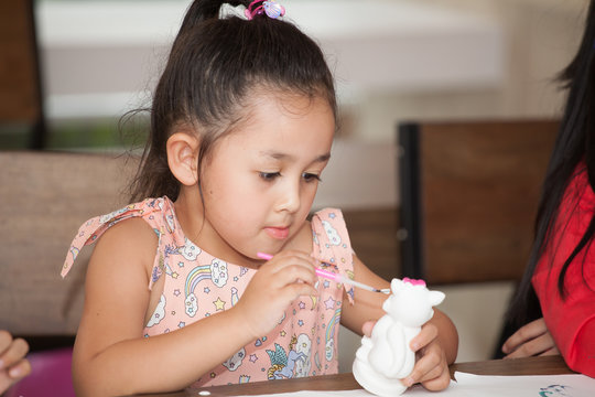 Cute little girl student painting a ceramic pottery model  in classroom school . kid artist . child sitting at desk preschool . Early education . Children in kindergarten.