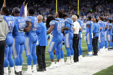 Detroit Lions players and staff lock arms during the playing of the national anthem before their NFL football game against the New York Jets in Detroit, Michigan