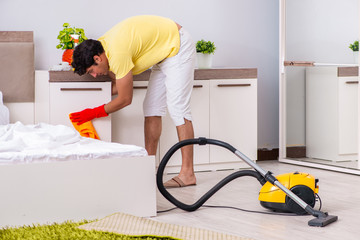Young handsome man cleaning in the bedroom