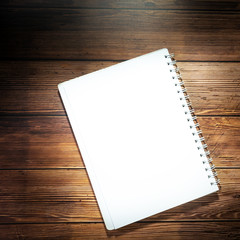 Blank notebook on wooden table. Opened notepad on top of a desk. Blank Catalog on the wooden background for your design.