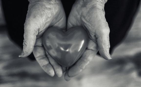 elder woman holding heart