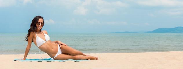 Beautiful young Asian woman in white bikini on summer beach banner background