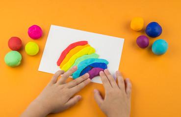 child mold from colored plasticine.Children's hand