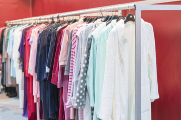 many bathrobes any colors. Racks and hangers with cotton and bamboo dressing gowns. Dressing gowns on the hanger in the store